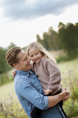 Finland, Uusimaa, Raasepori, Karjaa, Father holding in arms his daughter (6-7)