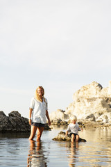 Sweden, Gotland, Faro, Mother with son (2-3) next to rocks on Baltic Sea