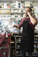 Finland, Man talking on phone in bicycle shop