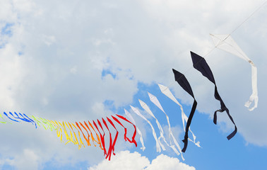 Ribbon is of multi-colored flags against the blue of the cloudy sky