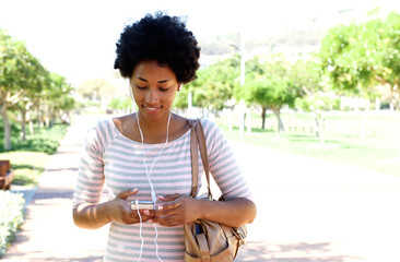 Woman walking in park listening to music on phone