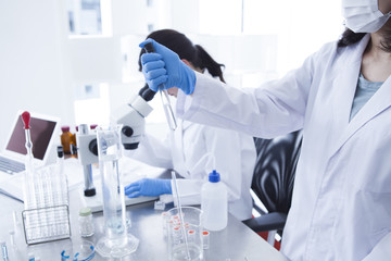 Woman wearing a white coat has a test tube