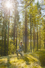 Finland, Etela-Savo, Huttula, Young woman sitting on bucket in forest
