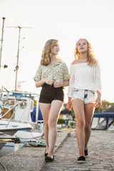 Sweden, Blekinge, Hallevik, Two teenage girls(14-15, 16-17) walking at marina bay