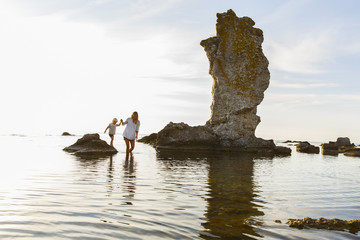 Sweden, Gotland, Faro, Mother with son (2-3) wading among rocks on Baltic Sea