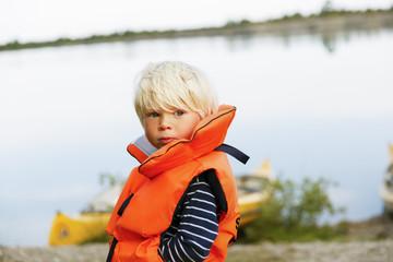 Sweden, Gotland, Farosund, Little blonde boy (2-3) wearing lifejacket standing on riverbank