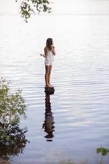 Sweden, Vastmanland, Bergslagen, Svartalven, Girl (8-9) standing on rock in river