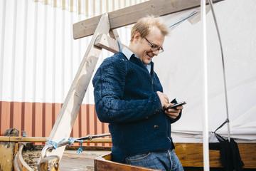 Sweden, Vastra Gotaland, Man using smartphone on boat