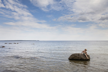 Boy sitting on rock in ocean