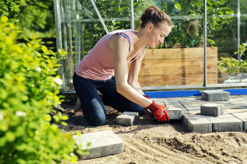 Finland, Paijat-Hame, Mid adult woman paving in front of greenhouse