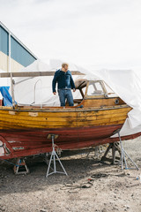 Sweden, Vastra Gotaland, Man renovating wooden boat