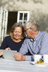 Sweden, Sodermanland, Senior couple discussing finances using digital tablet at table in backyard
