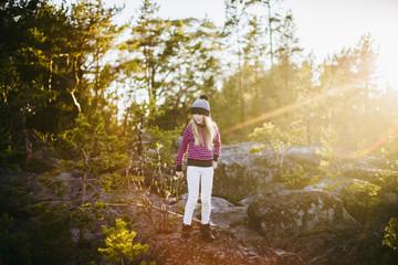 Sweden, Medelpad, Sundsvall, Juniskar, Portrait of girl (10-11) standing in forest on sunny day