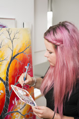 Sweden, Young woman with pink hair painting on canvas