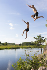 Sweden, Ostergotland, Mjolby, Young man and teenage boy (16-17) jumping into Svartan River