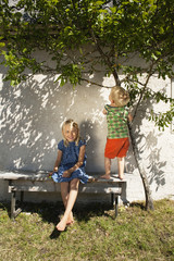 Sweden, Gotland, Faro, Girl (8-9) with brother (2-3) on back yard bench