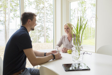 Sweden, Man and woman sitting and drinking at home