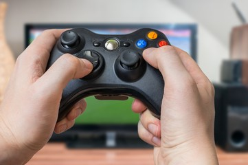 Young man is playing video games and holds joystick or controller.