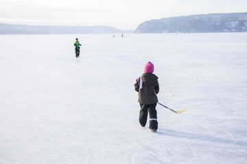 Sweden, Vastergotland, Lerum, Lake Aspen, Siblings (6-7, 8-9) playing ice hockey on lake