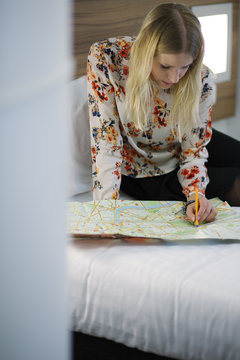 United Kingdom, England, London, Young woman examining map on bed