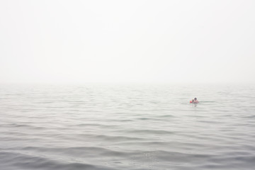 Sweden, Gotland, Ljugarn, Man and boy (4-5) swimming in foggy sea