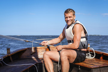 Portrait of smiling young man sitting in boat