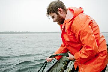 Sweden, Skane, Skane, Yngsjo, Man fishing in sea
