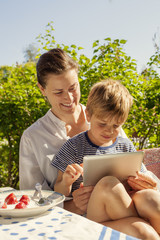 Smiling mother and son using digital tablet outdoors