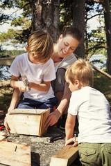 Sweden, Uppland, Runmaro, Barrskar, Mother helping sons (4-5, 6-7) to build birdhouse