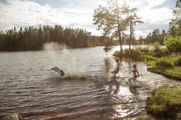 Sweden, Narke, Kilsbergen, Bjorktjarn, young man with children (10-11, 12-13) playing in lake at sunset