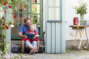 Father and daughter using digital tablet while sitting on doorstep