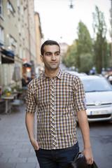 Sweden, Stockholm, Skanegatan, Sodermalm, Portrait of man with hand in pocket