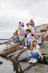 Sweden, Uppland, Roslagen, Big family having picnic on rocks at seaside