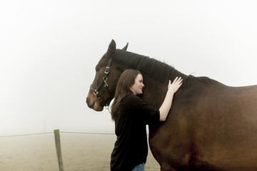 Sweden, Skane, Mid-adult woman with horse on dirt road in fog