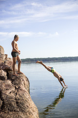Finland, Uusimaa, Baltic Sea, Porvoo, Boys (8-9, 10-11) jumping into water from rock