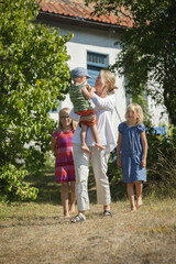 Sweden, Gotland, Faro, Mother with daughters (8-9, 10-11) and son (2-3) in backyard