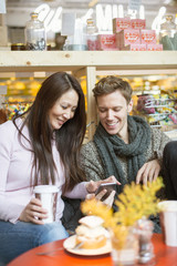 Sweden, Man and woman using smart phone in shop
