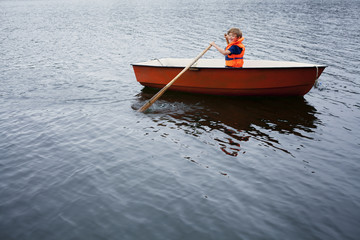 Boy rowing boat in sea