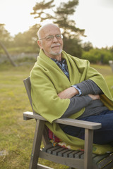 Portrait of senior man sitting on chair outdoors