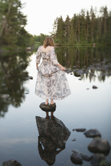 Sweden, Vastmanland, Bergslagen, Svartalven River, Woman on stone in still water