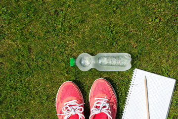 Fitness concept, pink sneakers, notebook with pencil and bottle of cold water on green grass, top view