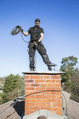 Sweden, Sodermanland, Nacka, Mid-adult man cleaning chimney