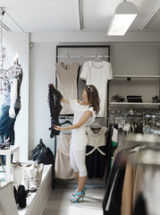Finland, Helsinki, Woman choosing clothes in shop