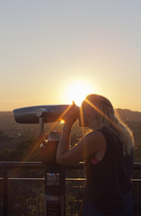 USA, California, Los Angeles, Griffith Observatory, Woman using coin-operated binoculars at sunset