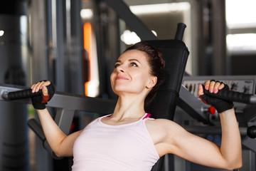 Young slim woman doing chest fly exercise in gym