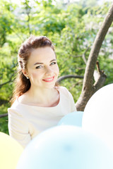 Beautiful young woman with balloons sitting on tree