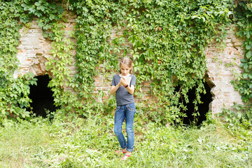 Small teenage girl standing near old brick ruins