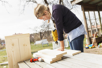 Sweden, Sodermanland, Jarna, Woman working in garden