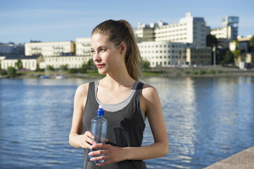 Sweden, Stockholm, Sodermalm, Norra Hammarbyhamnen, Young woman with water bottle, Hammarby Sjostad in background