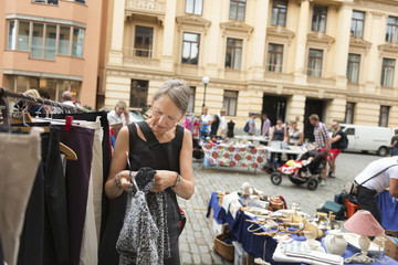 Sweden, Stockholm, Normalm, Blasieholmstorg, Portrait of mature woman choosing dress at flea market